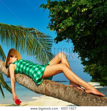 Woman in green dress lying down on a palm tree at tropical beach, Maldives