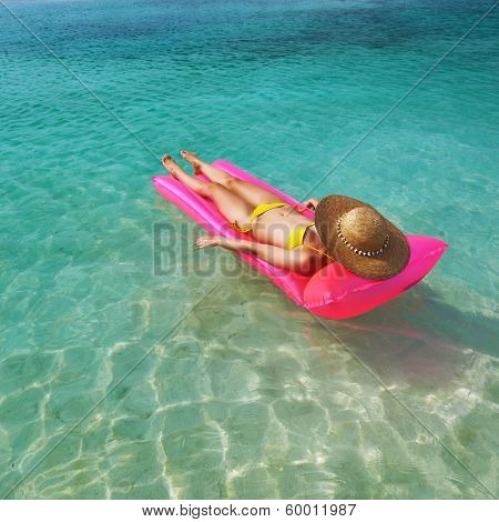 Woman relaxing on inflatable mattress near the beach