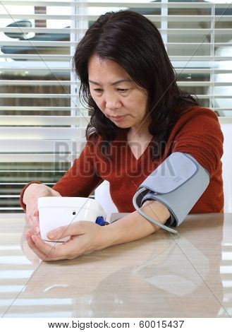 Asian woman testing her bllod pressure at home poster