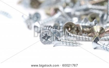 Zinked and anodized screws. Blurred. Isolated on a white background. poster