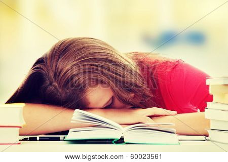 Teenage girl studying at the desk being tired, isolated on white