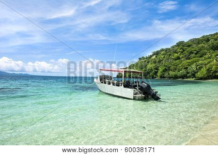 A scuba diving boat is anchored in a beautiful tropical bay of turquoise water and a bright, blue vibrant sky with patchy clouds.