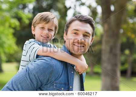 Side view portrait of a father carrying young boy on back at the park