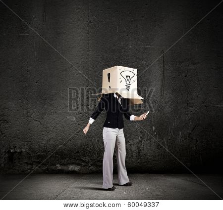 Businesswoman using mobile phone wearing carton box on head