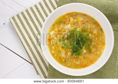 A bowl of thick fresh pea soup with herbs vegetarian on wooden background poster