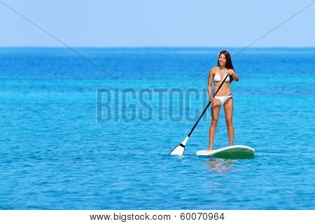 Stand up paddle board woman paddleboarding on Hawaii standing happy on paddleboard on blue water. Young mixed race Asian Caucasian female model on Hawaiian beach on summer holidays vacation travel.