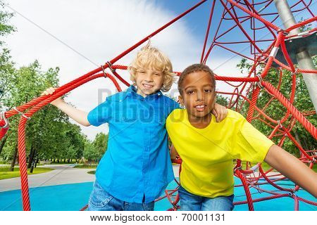 Portrait of two boys stand on red ropes