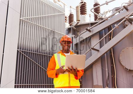 african electrician using laptop in front of transformer