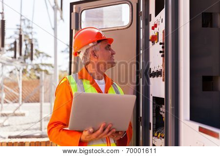 experienced senior electrician working on a transformer in substation