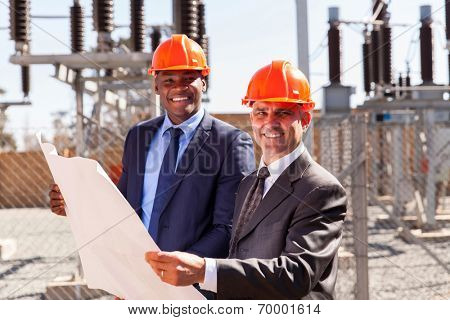 portrait of successful industrial managers holding blueprint at substation