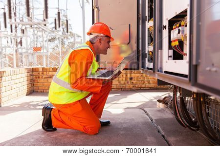 successful mid age electrician kneeing in front of transformer