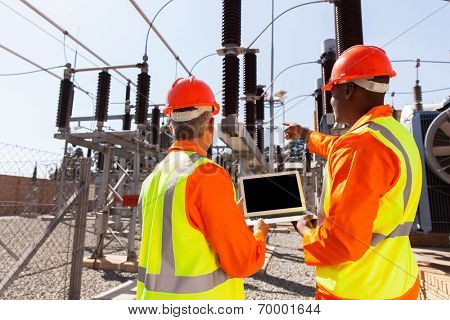 rear view of electricians with laptop pointing in substation