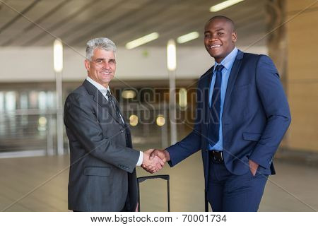 portrait of business travellers greeting at airport