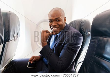 young african american businessman holding cell phone on airplane