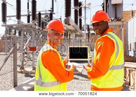 happy electrical engineers holding laptop computer in power plant