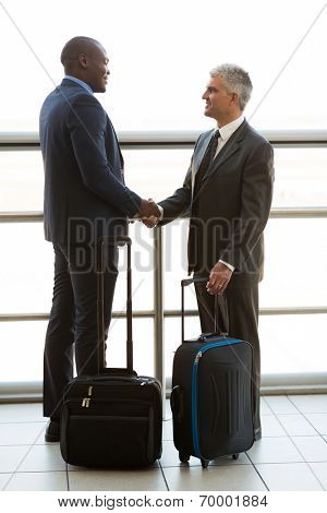 cheerful business travellers meeting at airport