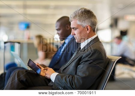 senior male passenger at airport using tablet computer while waiting for his flight