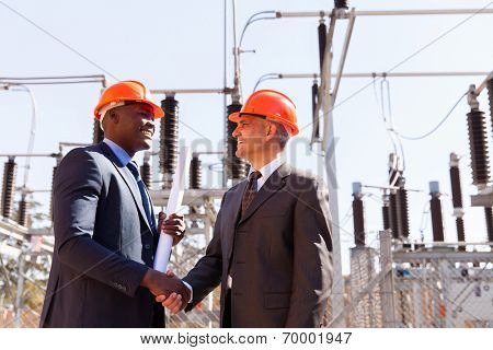 two cheerful businessman handshaking in electric substation
