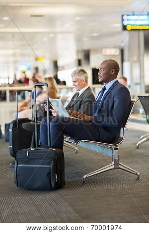 thoughtful african businessman waiting for flight at airport