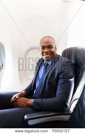 portrait of young african american businessman on airplane