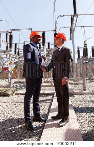 power company managers handshaking in electrical substation