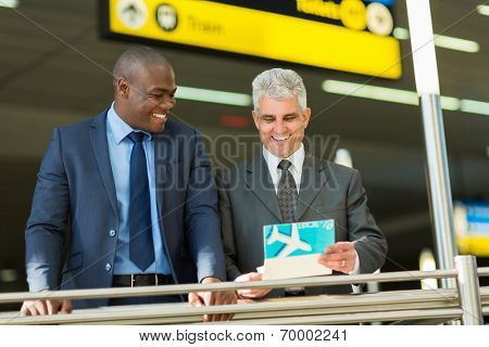 cheerful businessmen holding air ticket at airport