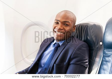 smiling african american airplane passenger relaxing during flight
