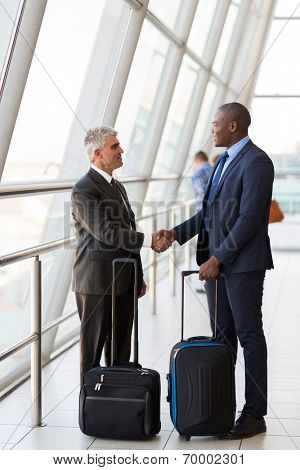 professional businesspeople handshaking at airport