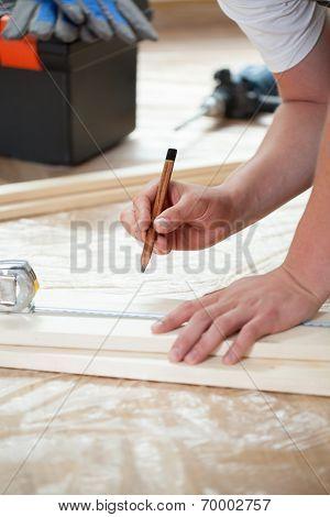 Man Measuring Boards During Renovation