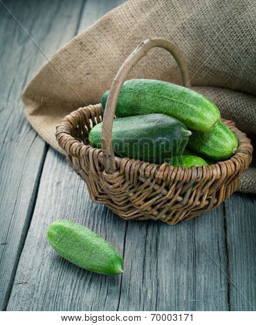 Harvest Cucumbers In A Basket On The Wooden Background