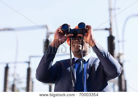 african american electrical manager using binoculars looking at substation