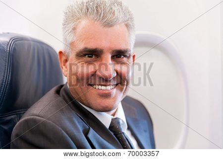 portrait of smiling senior businessman on airplane