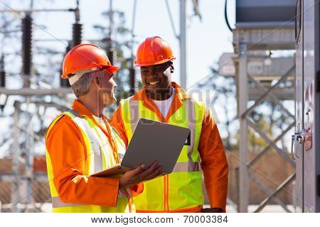 happy electricians using laptop computer in electrical substation