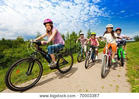 Two girls and boys in helmets ride bikes together