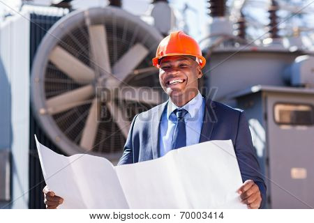 cheerful young african electrical manager holding blueprint in electric substation