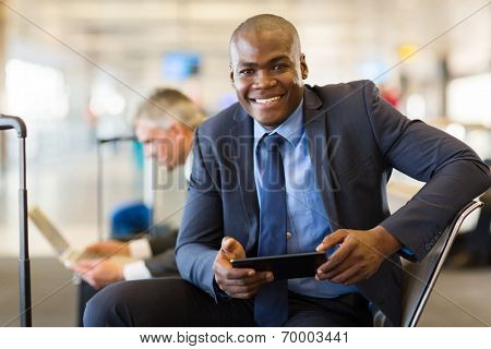 happy african business traveler at airport using tablet computer while waiting for flight