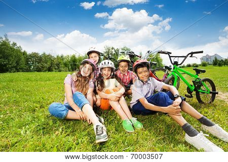 Happy kids in helmets sit on grass and smile