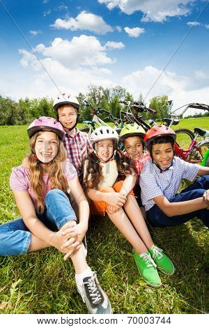 Children in helmets laugh, sit together on grass