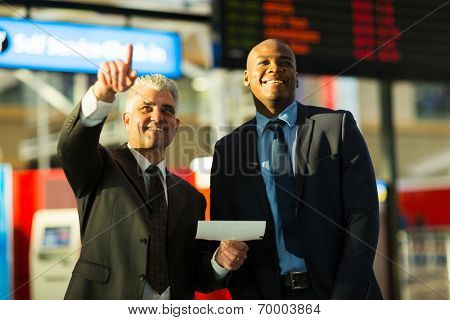 handsome business travellers pointing at flight information board