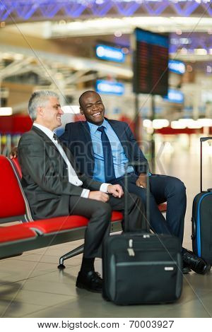 cheerful business travellers waiting for their flight at airport