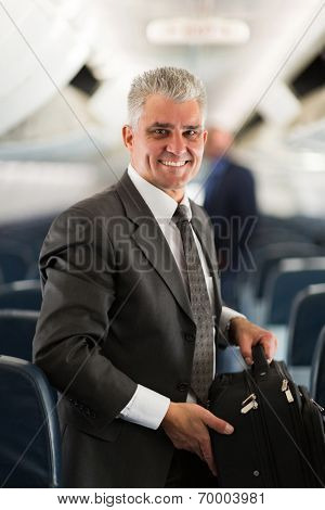 good looking middle aged businessman carrying bag on airplane