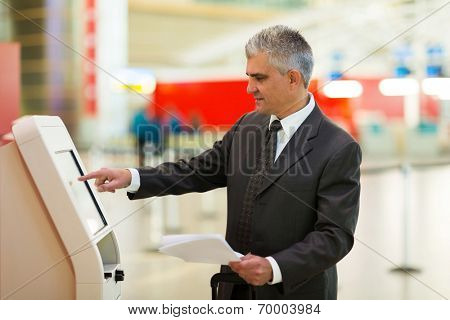 mid age business traveller using self help check in machine at airport