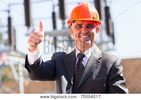 portrait of happy middle aged male industrial manager giving thumb up at substation
