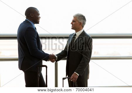 two professional businessmen hand shaking at airport