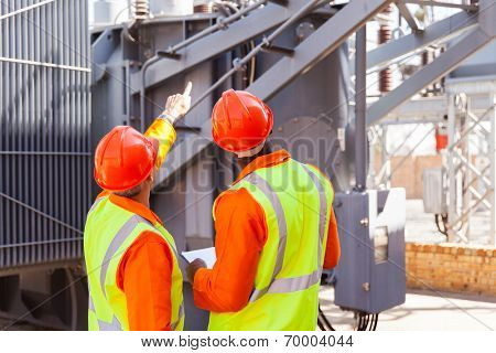 rear view of electrical engineers working in substation