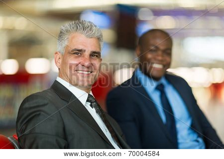 middle aged businessman and colleague waiting for flight at airport