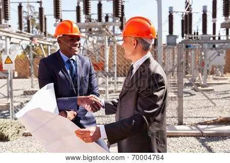 friendly business partners handshaking in electrical substation