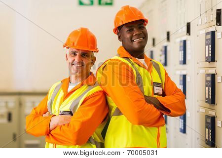 portrait of handsome industrial engineers with arms crossed in power plant control room
