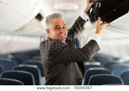 portrait of middle aged business traveler putting luggage into overhead locker on airplane