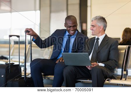 cheerful businessmen using laptop computer at airport